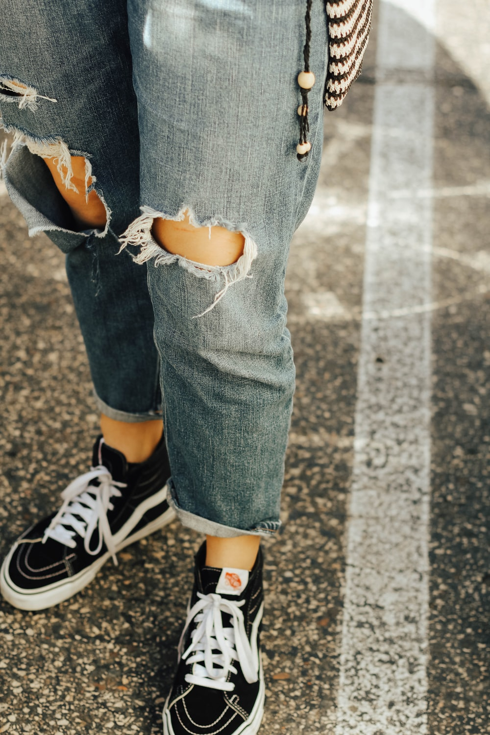 close-up photo of blue denim jeans and pair of black Vans sneakers