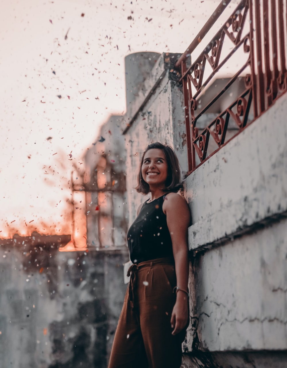 smiling woman standing in front of gray concrete wall