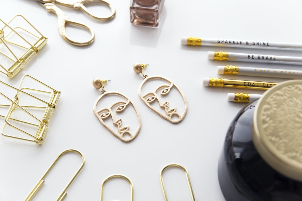 gold-colored face-cutout earrings