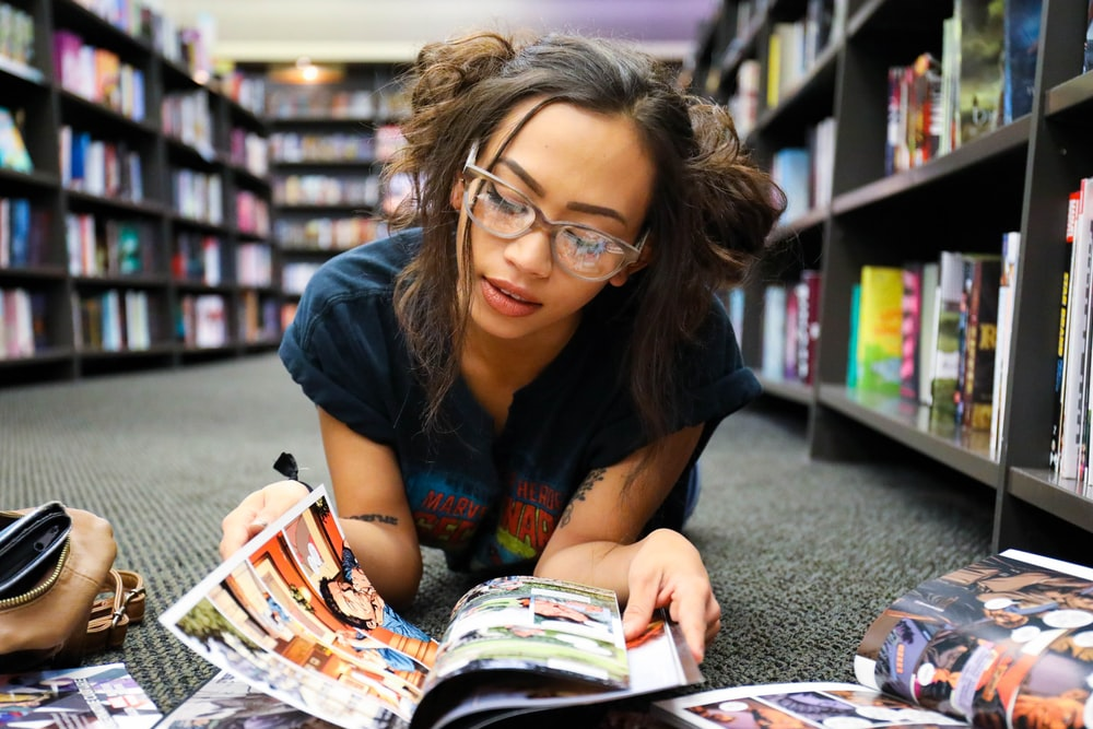 woman in black, blue, and red shirt lying on surface while reading magazine