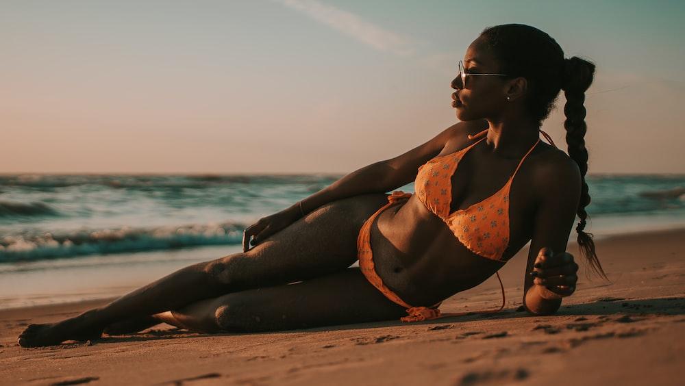 woman wearing bikini while lying on sand by the seashiore