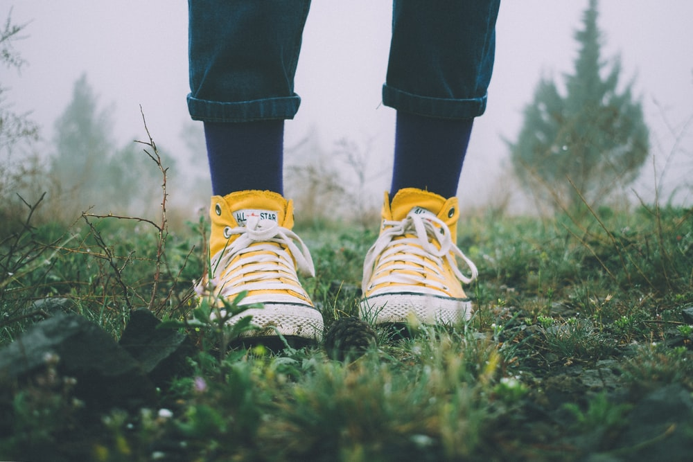 person in black pants and yellow sneakers standing on grass field