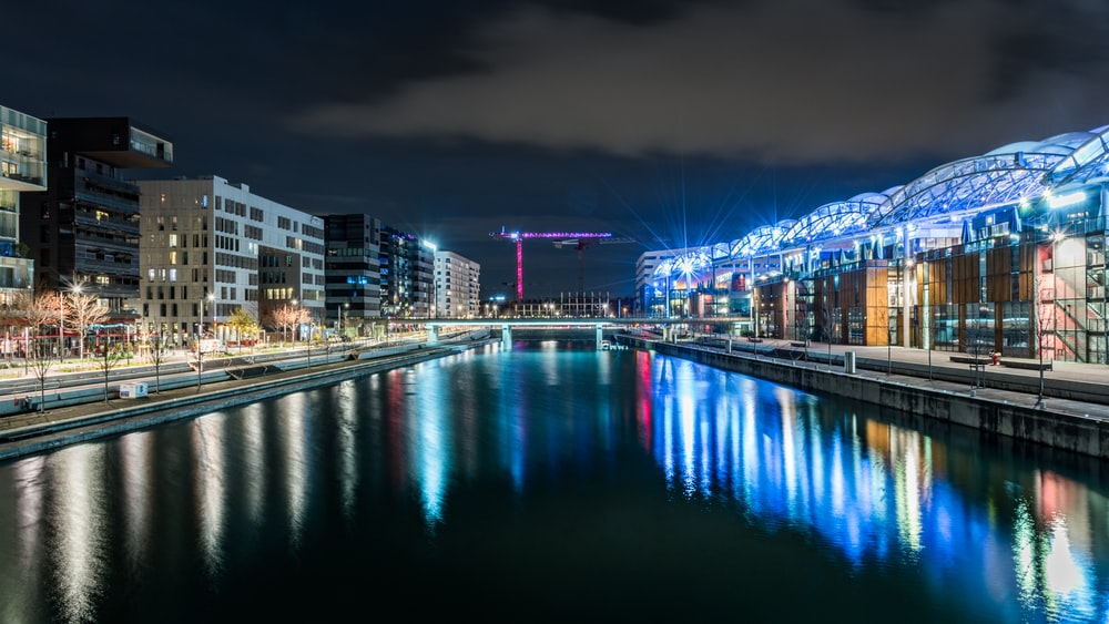lights reflecting on glassy river at the city