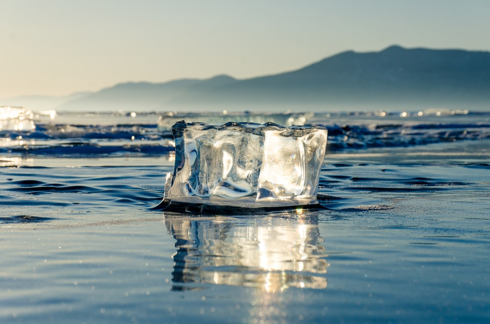 ice block on calm body of water during daytime