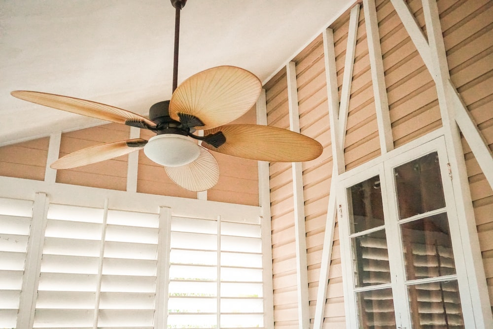 brown ceiling fan with lamp inside house