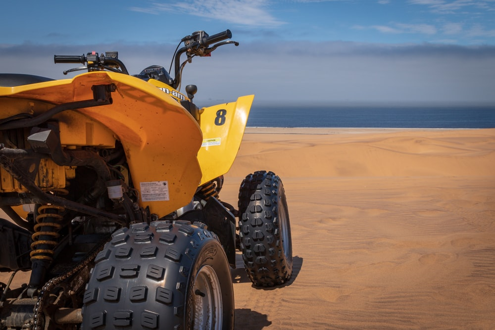 shallow focus photography of yellow and black ATV