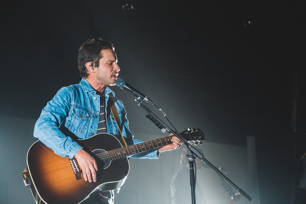 man using guitar while performing on stage