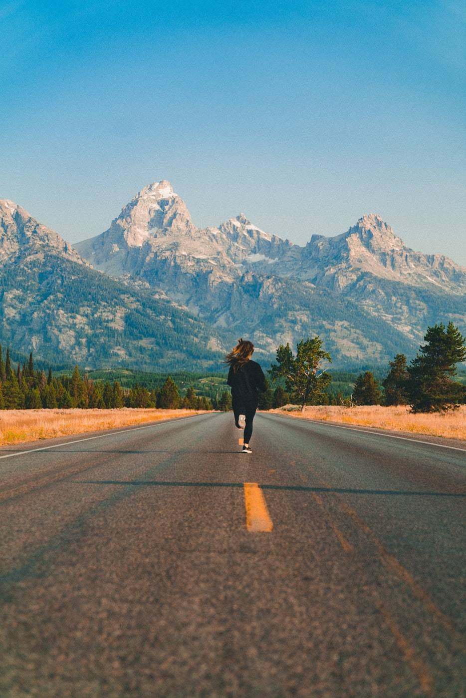 a woman running down the road in front of the Grand Teton National Park, Wyoming