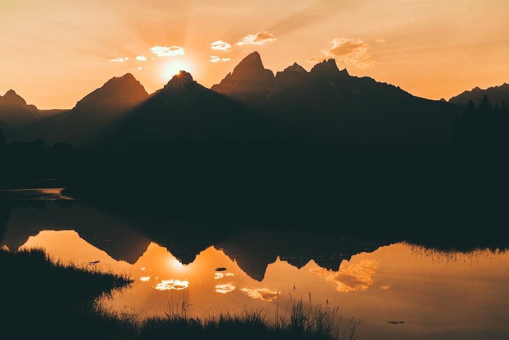 silhouette of mountain beside lake
