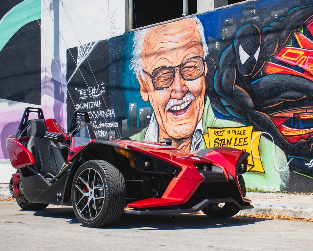 red and black sports car beside wall