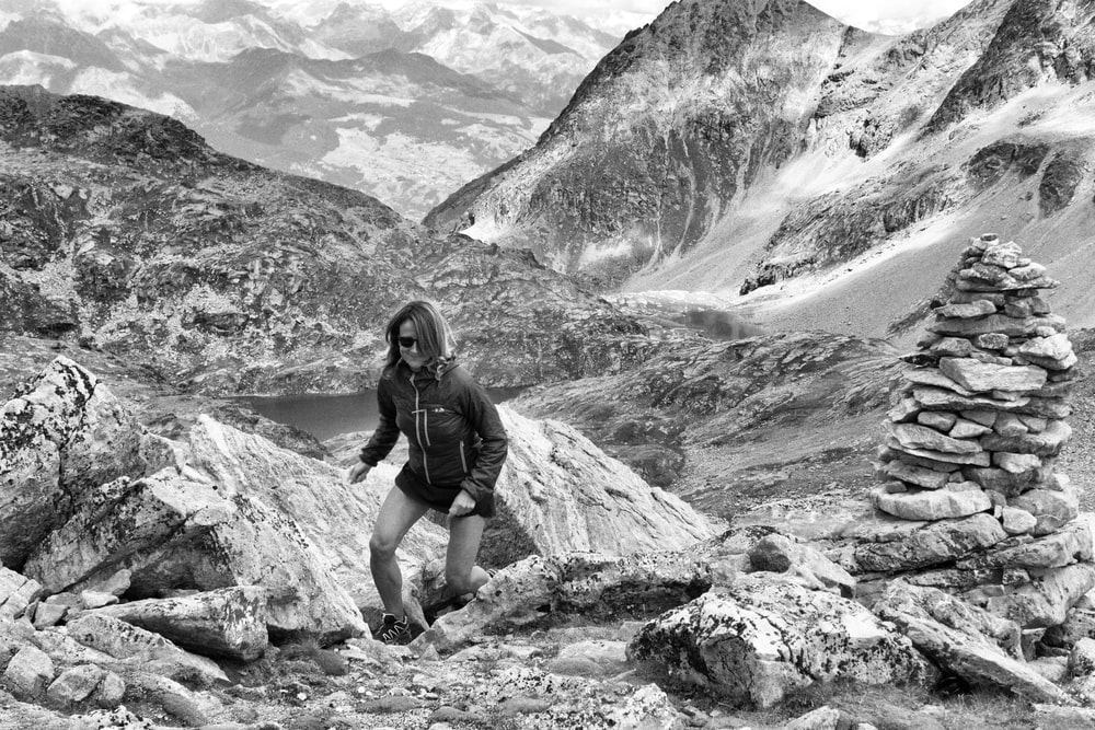 grayscale photography of woman climbing on mountain