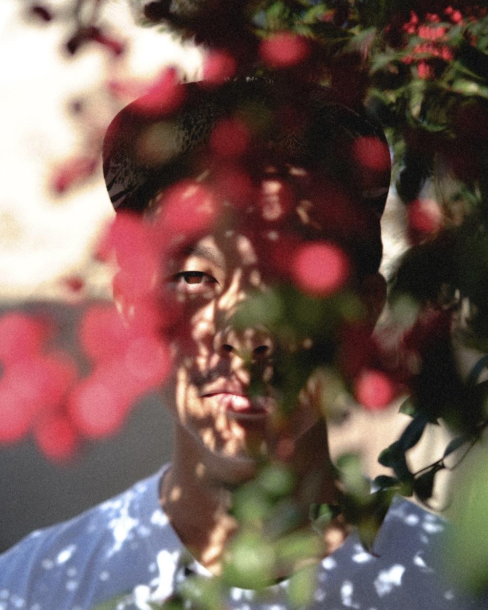 man in white crew-neck shirt posing near flowers