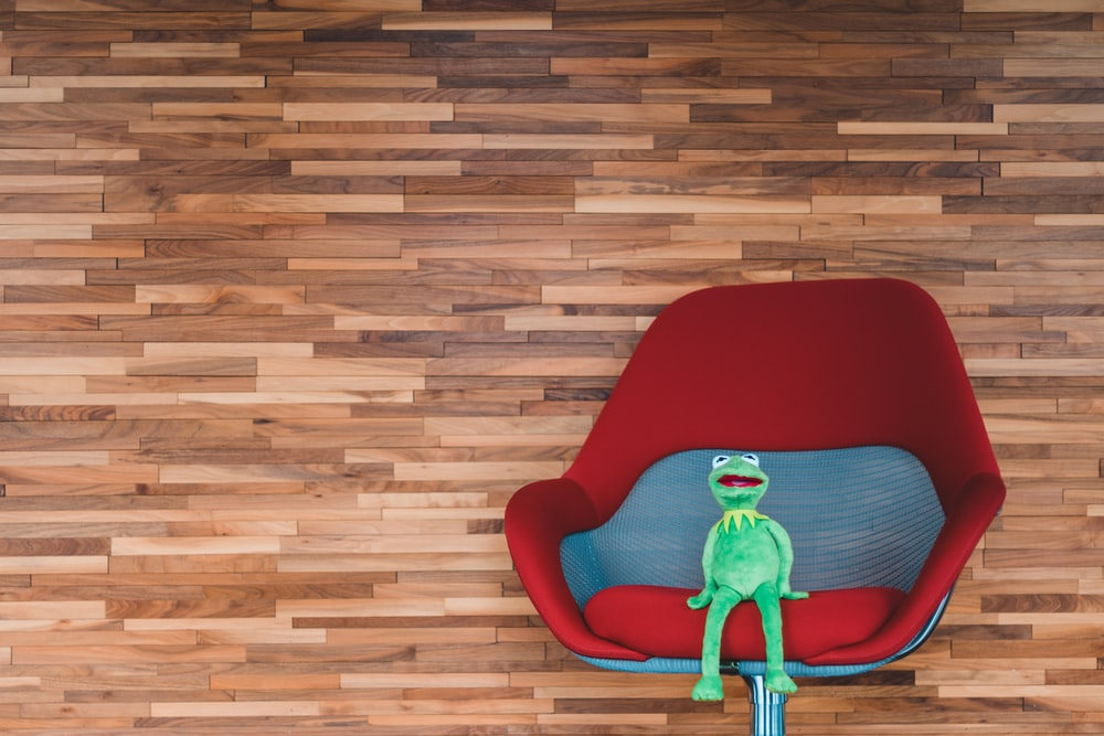 Kermit the frog plush toy on red swivel chair
