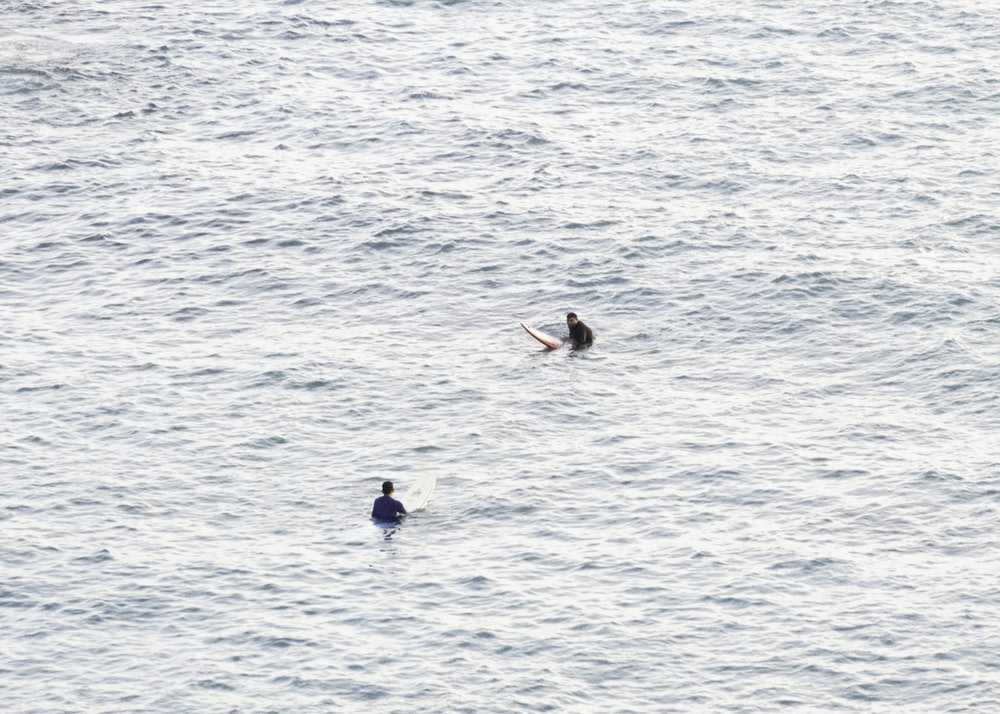 two people in body of water during daytime