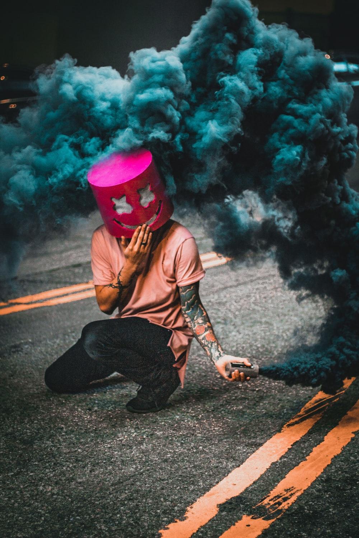 man wearing mask making blue smoke