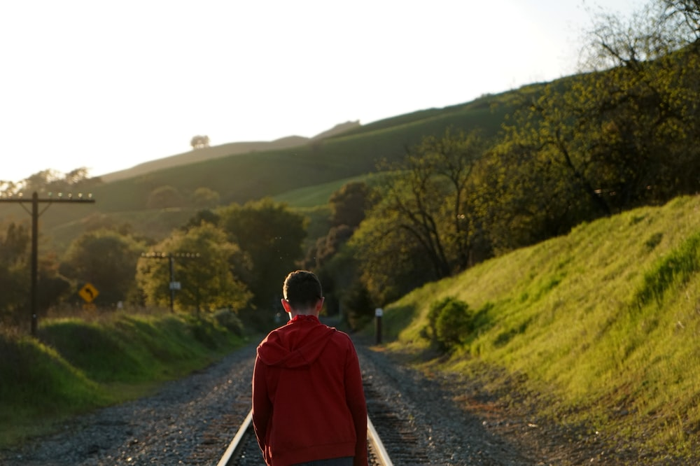 man standing on rail track