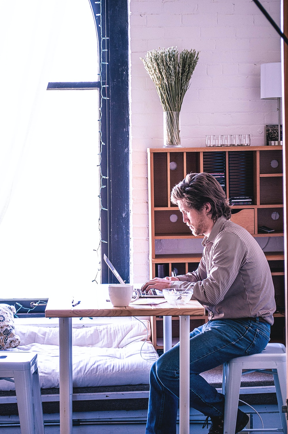 man sitting in front of table browsing laptop