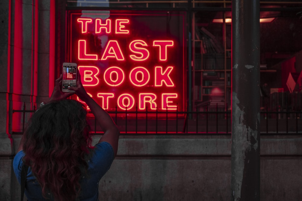 woman taking picture of neon signage