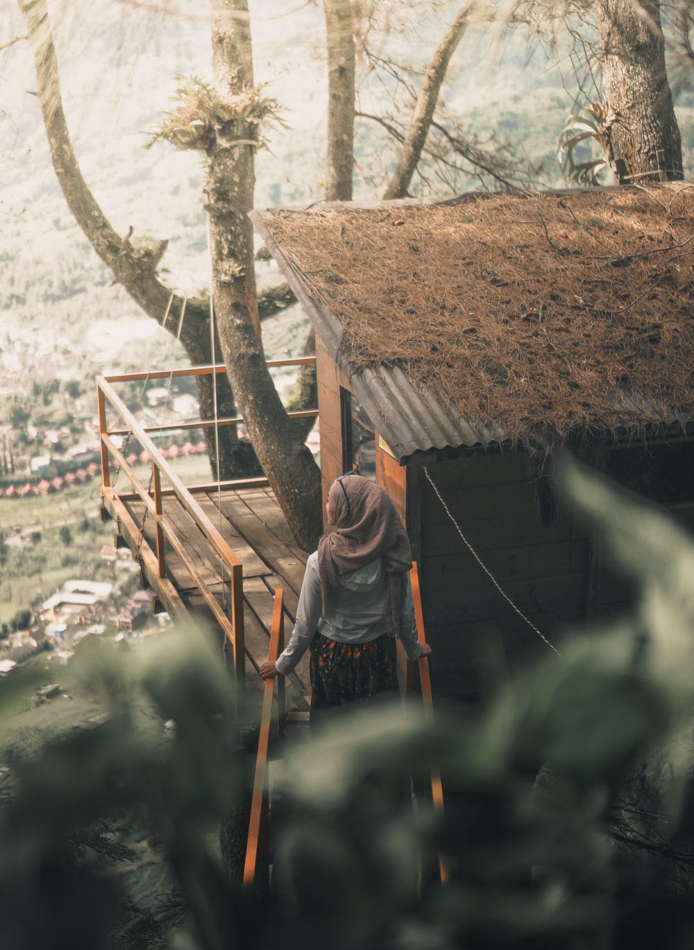woman wearing hijab standing beside house