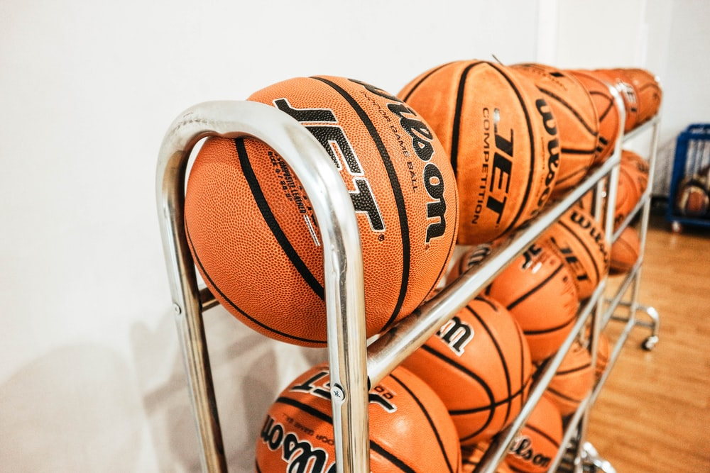 pile of basketballs beside wall