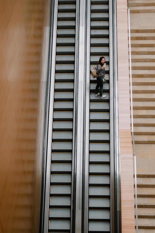 high-angle photography of person on escalator