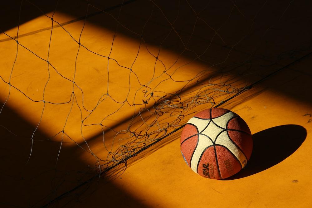 basketball near broken chain fence in dim light