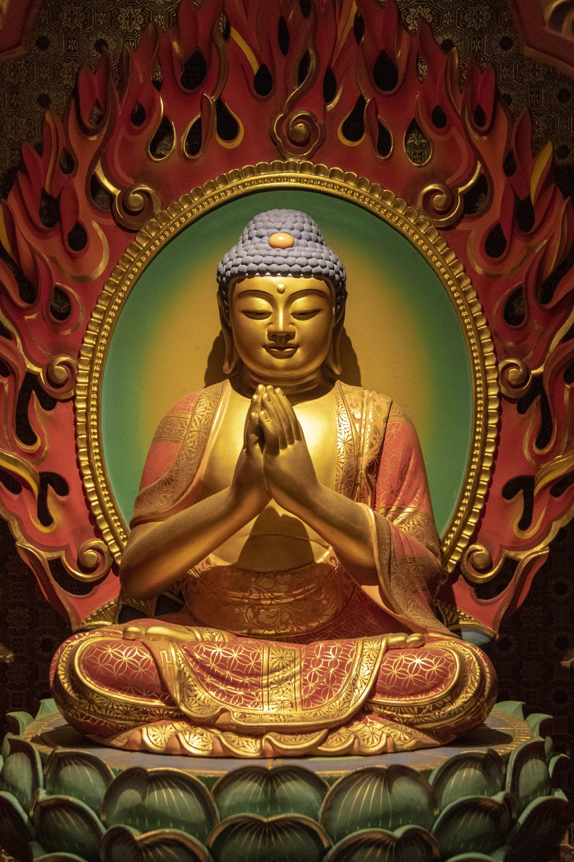 red and gold great buddha ceramic figurine in closeup photo