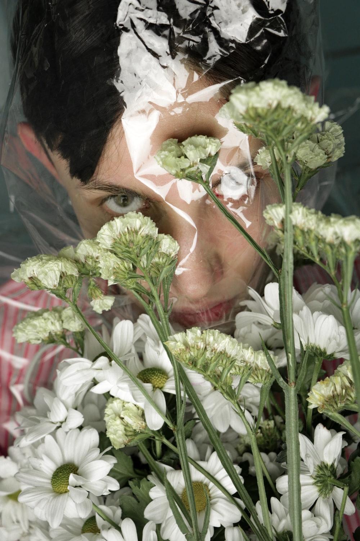woman taking selfie behind flowers