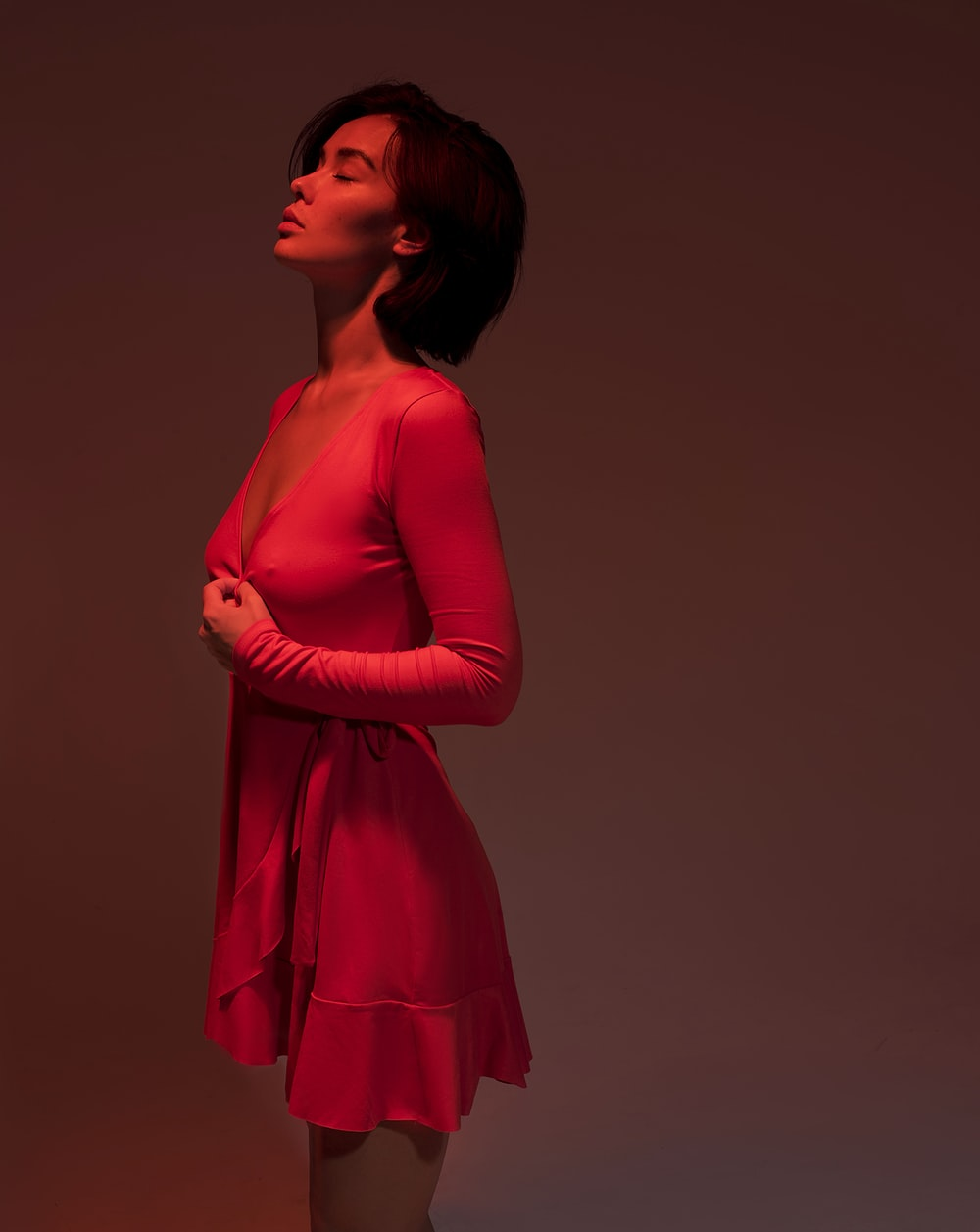 standing woman in pink long-sleeved dress
