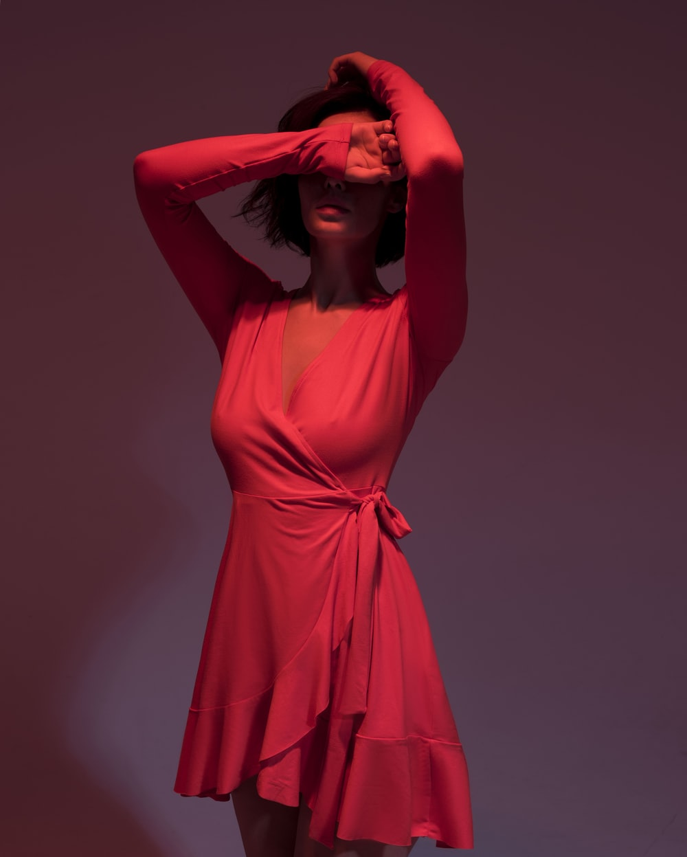 woman wearing pink long-sleeved dress covering her face