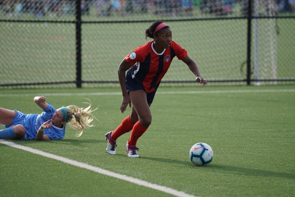 woman in red jersey kicking the ball