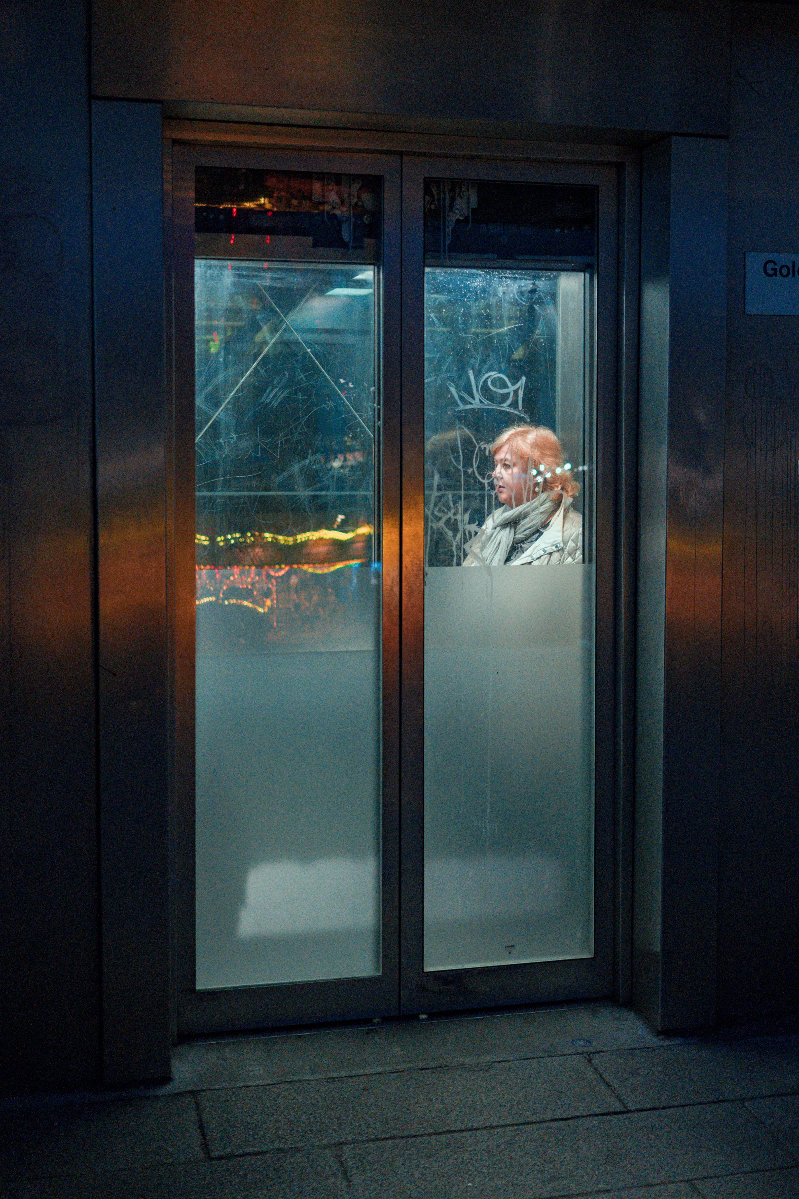 person inside grey metal framed clear glass door