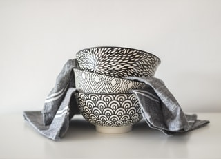 three black and white round ceramic bowls and grey textile