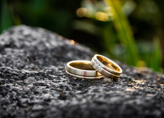 selective focus photography of two gold-colored rings on black stone during daytime