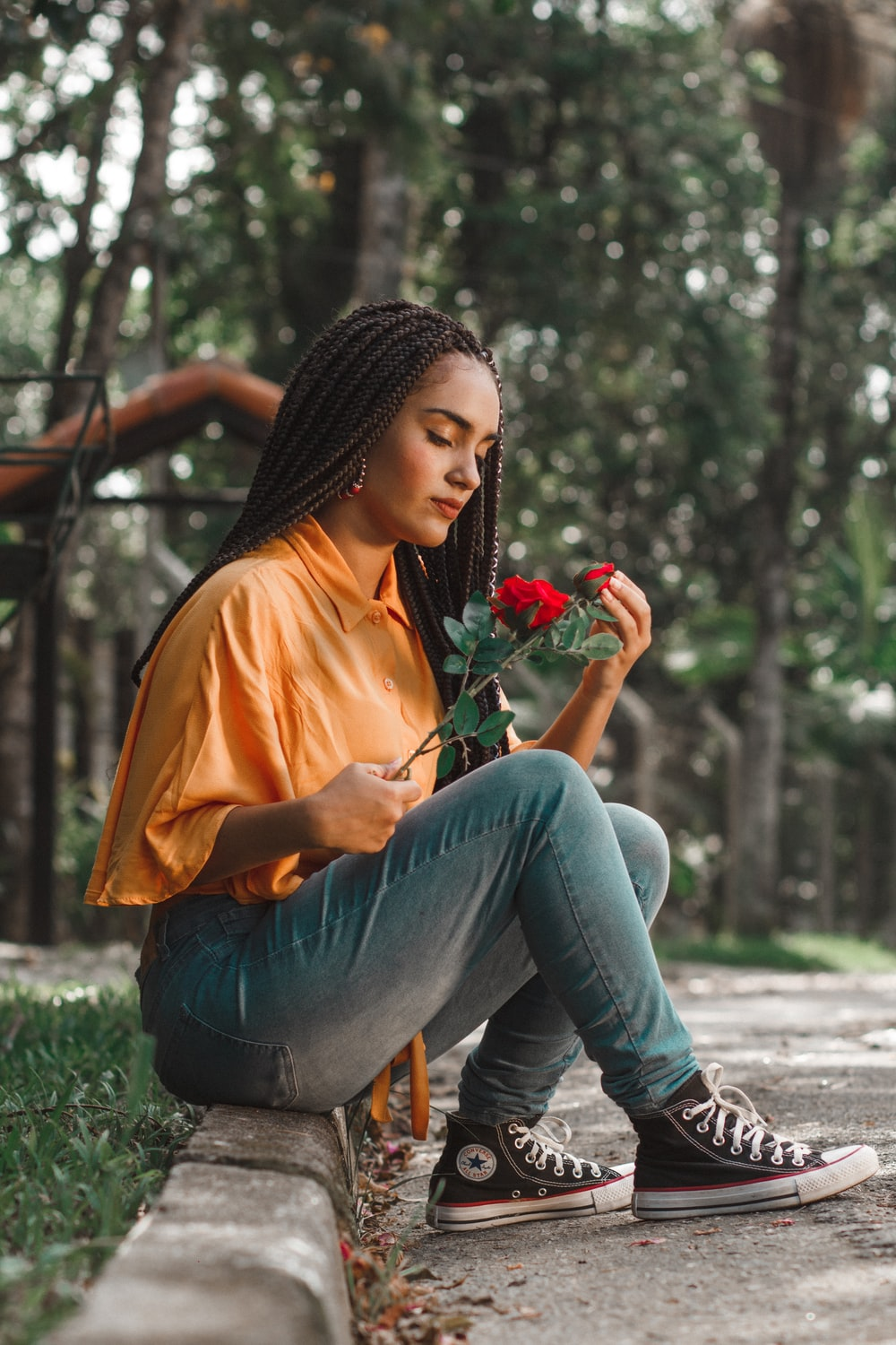 woman holding flower while sitting on ground during daytime