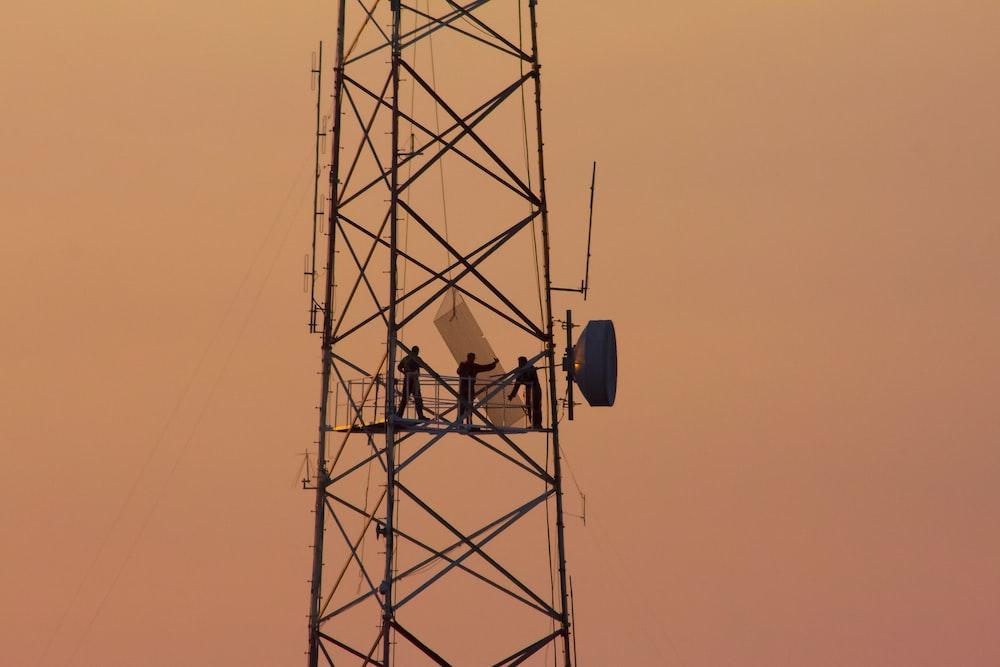 three people standing on crane tower