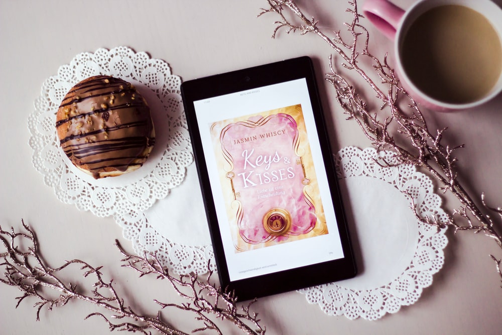 tablet showing Keys Kisses card between filled cup and dessert