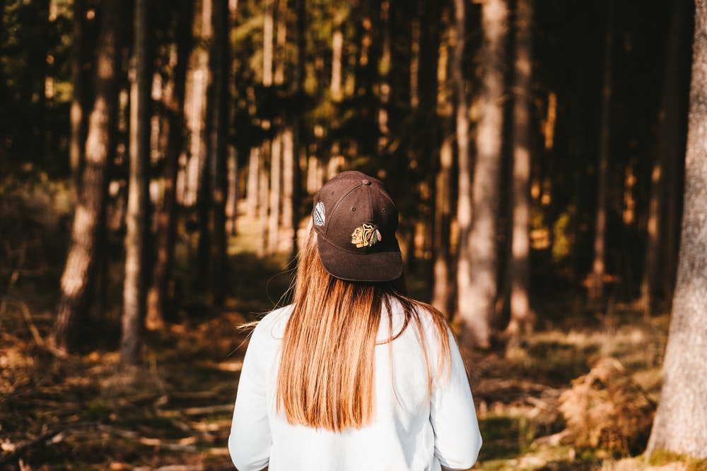 person wearing black cap standing in jungle