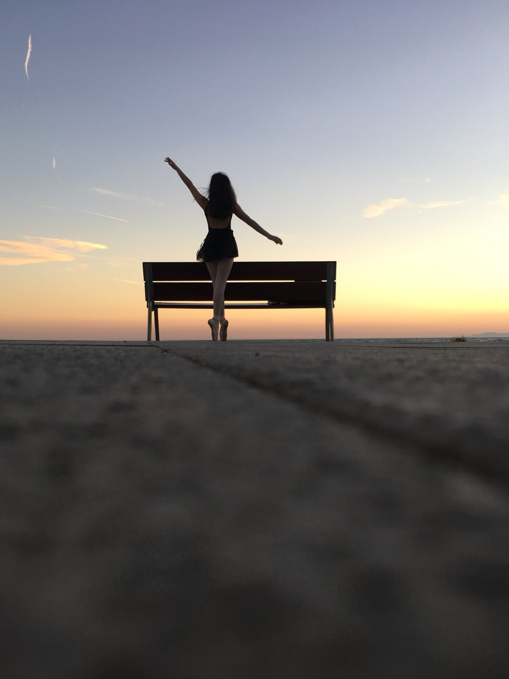 silhouette photography of woman standing on bench