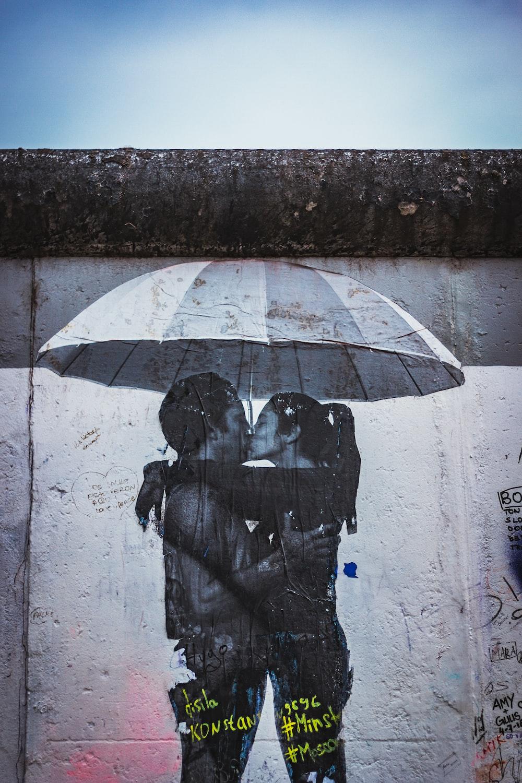man and woman kissing under umbrella photo