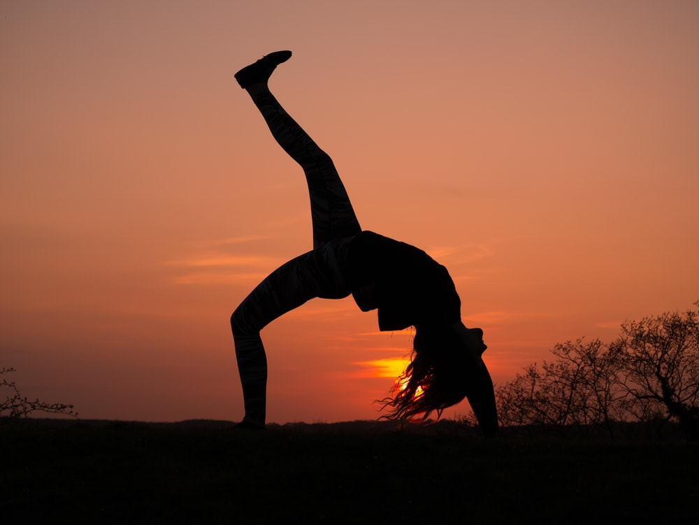 silhouette of person doing bending