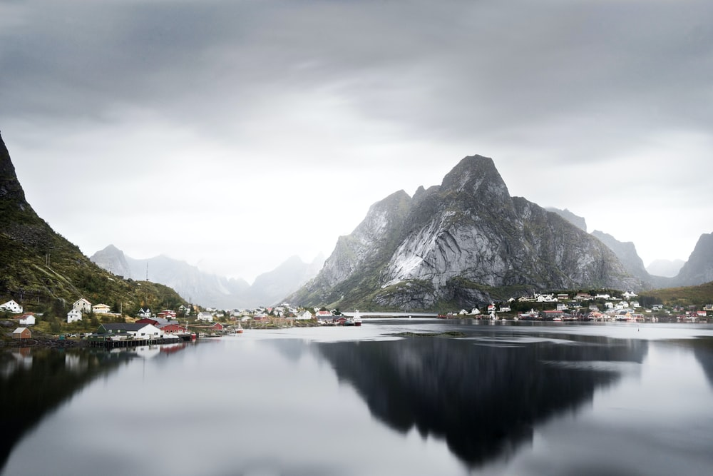 lake surrounded by houses and mountains