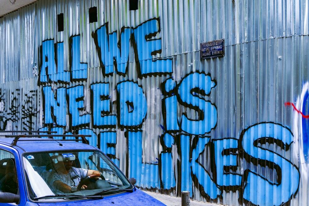 vehicle beside wall with graffiti