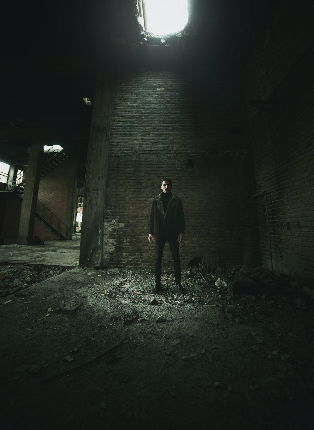 man standing near brick wall