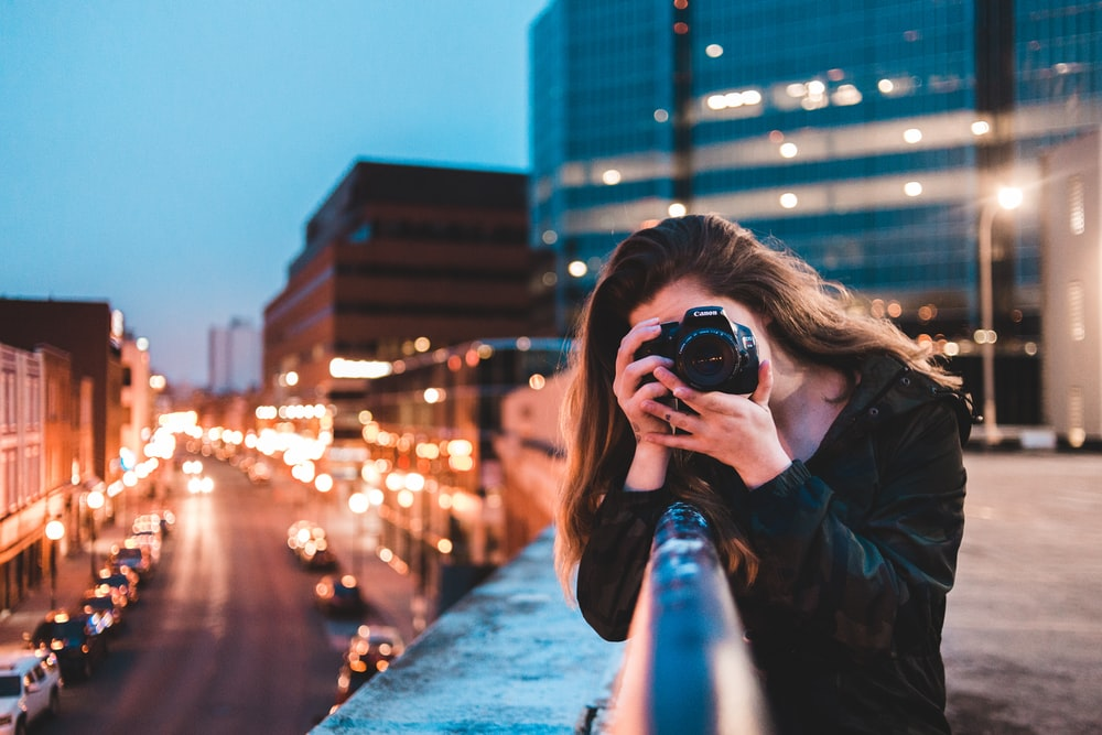 woman using black camera outdoors