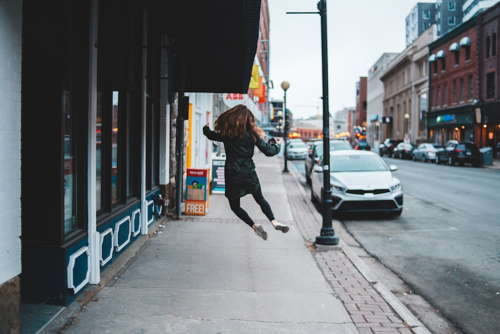 woman jumping infront of parked white vehicle