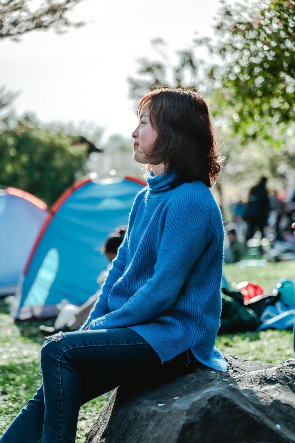 woman in blue sweater sitting on rock