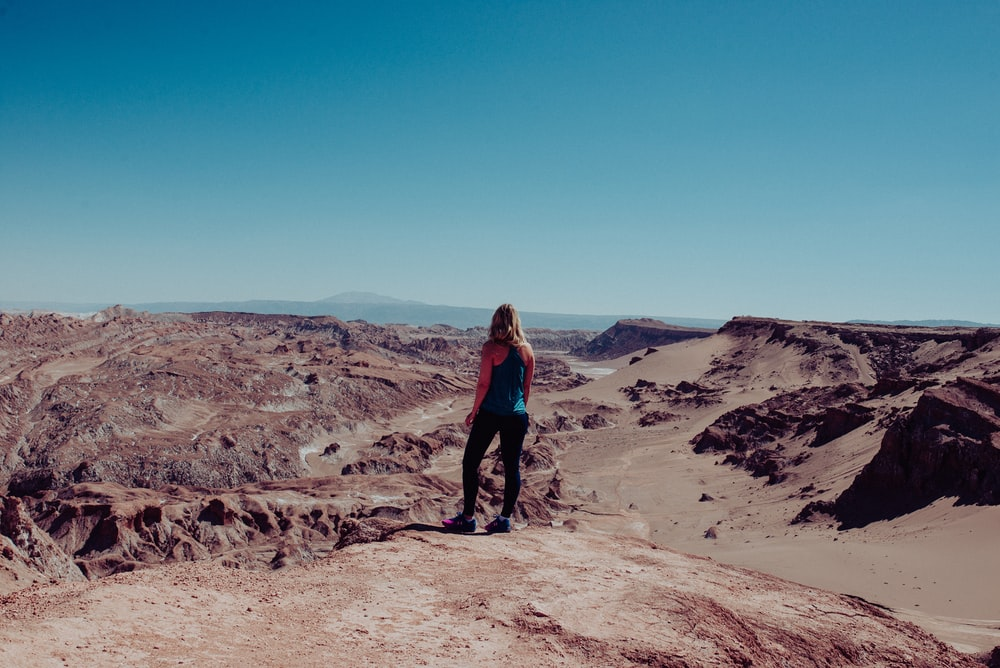woman on black dress atop of canyon looking at the mountainous terrain during daytime