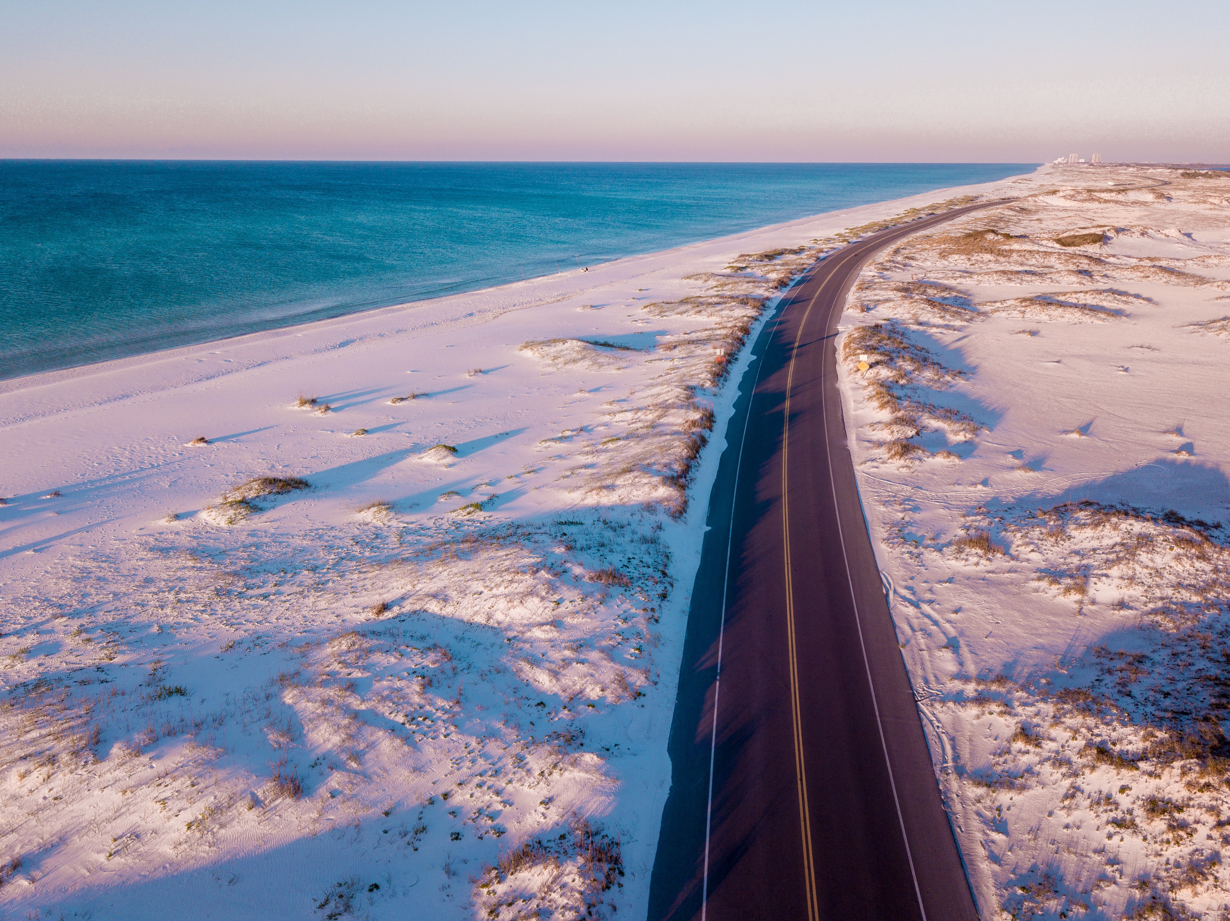 bird's eye view of road between snow covered grass