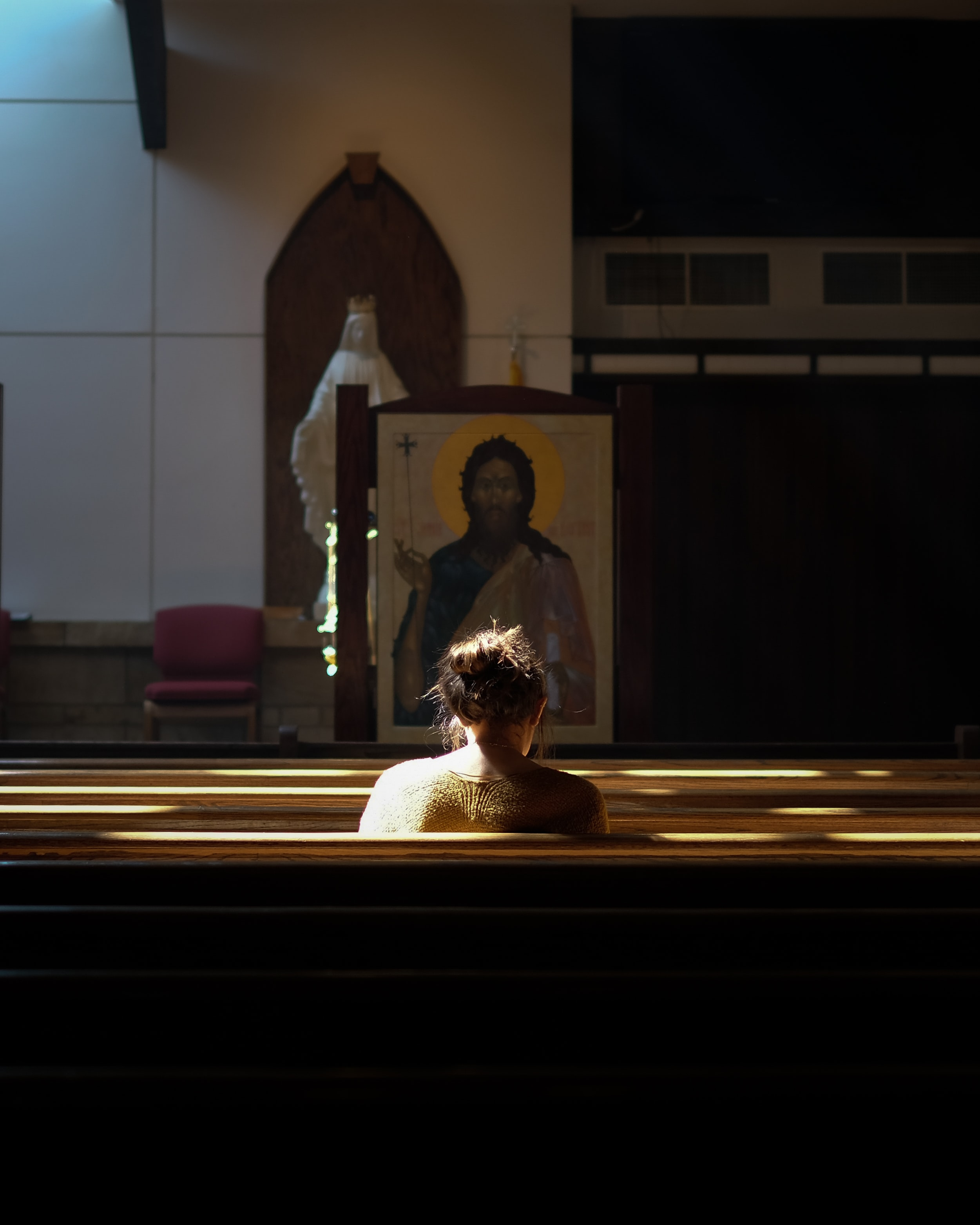 woman sitting on church pew during daytime